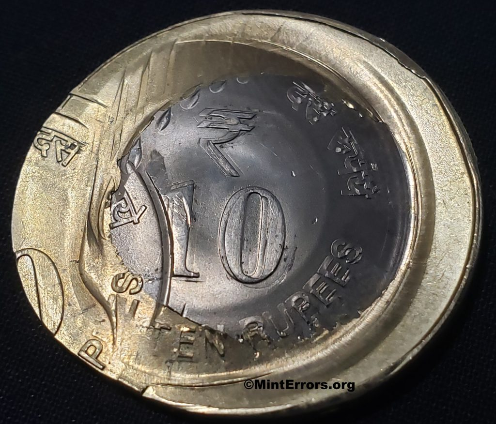 The Obverse of a unknown date Ten Rupees multi-struck, major mint error coin from India.